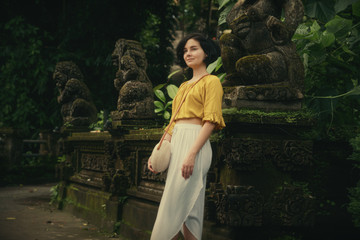 A girl in a white dress. Travel to Bali. Authentic architecture. Travel.