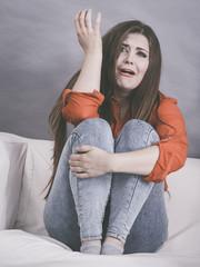 Worried woman sitting on sofa