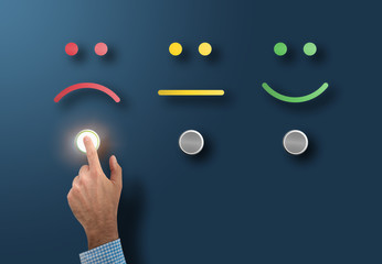 customer service rating and survey concept with dissatisfied customer touching interface button with sad face
