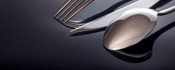 Knife and fork, spoon, on a black background