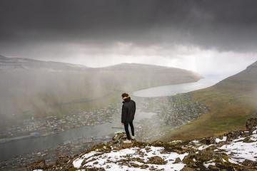 Wall Mural - Hiker on the Klakkur mountain above the city of Klaksvik on Faroe Islands