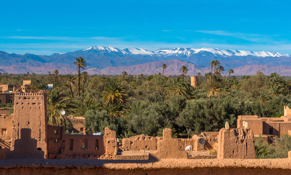 Kasbah Amridil in Skoura, Morocco, with the snowy Atlas Mountains in the distance