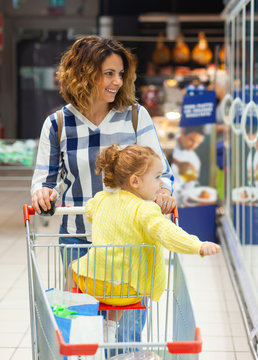 Mother and daughter shopping for groceries in supermarket.
