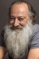 old man sixty, seventy, with a long beard with big smile on a dark background