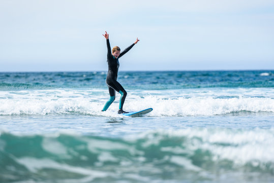 Surfer girl surfing with surfboard on waves in Atlantic ocean.
