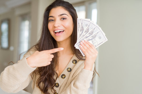 Young woman holding 50 dollars bank notes very happy pointing with hand and finger