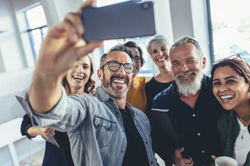 Multiracial group of people taking selfie at office Wall mural