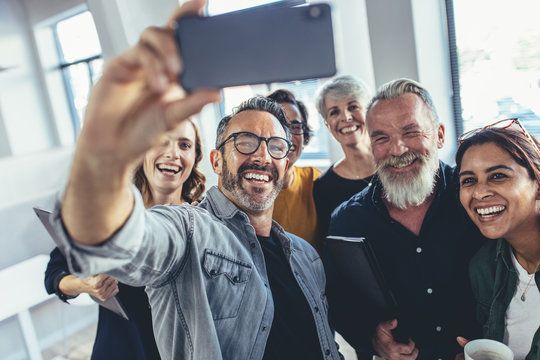 Multiracial group of people taking selfie at office