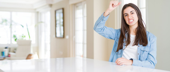 Wide angle picture of beautiful young woman sitting on white table at home angry and mad raising fist frustrated and furious while shouting with anger. Rage and aggressive concept.