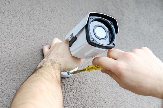 Technician worker installing video CCTV camera
