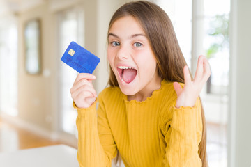 Beautiful young girl kid holding credit card very happy and excited, winner expression celebrating victory screaming with big smile and raised hands