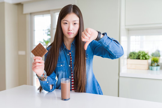 Beautiful Asian woman drinking chocolate milkshake and holding chocolate bar with angry face, negative sign showing dislike with thumbs down, rejection concept