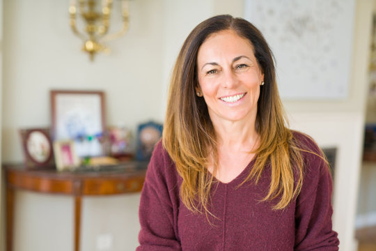 Beautiful middle age woman smiling at home