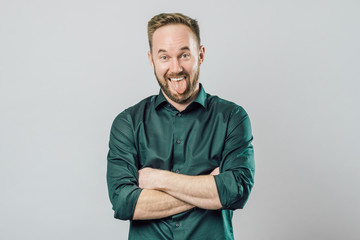 Portrait of funny adult man, sticking out tongue and smiling
