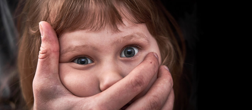 A frightened young girl with a grown man's hand covering her mouth. fear and despair in the child's eyes. kidnapping a little girl. child abuse concept.