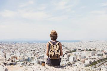 Traveler girl enjoying vacations. Young woman wearing hat looking at big city. Summer holidays, vacations, travel, tourism concept. Wall mural