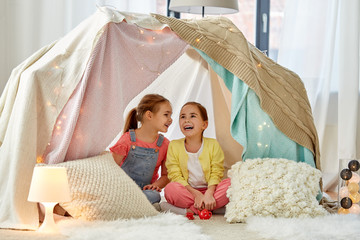 childhood and hygge concept - happy little girls playing tea party with toy crockery in kids tent at home