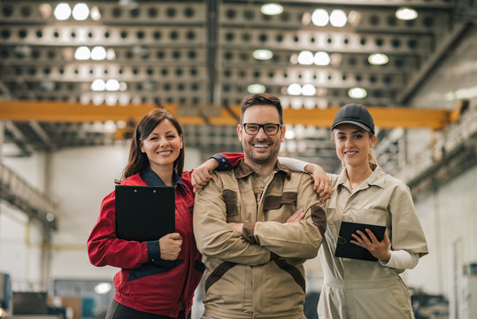Group portrait of a team of factory workers. Team leader, engineer and technician at factory hall, smiling at camera.