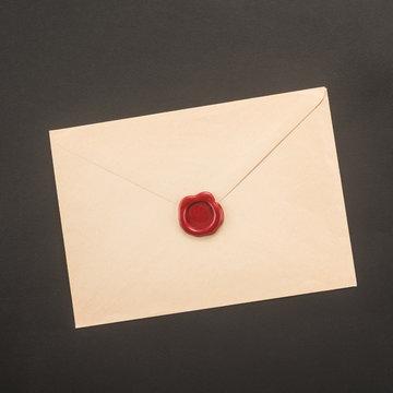 Envelope with wax seal on dark background