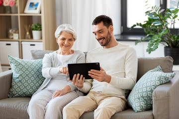family, technology and people concept - happy adult son teaching his senior mother how to use...
