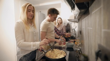 young people are cooking together in modern kitchen, two women are washing vegetables, other girl is stirring paste