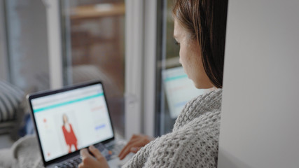 young woman is shopping online, watching pictures, choosing garment on a site using laptop, resting in her flat