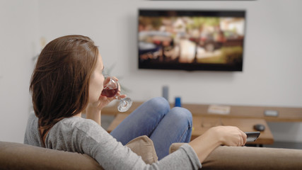 Young woman with glass of drink near TV in room