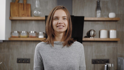 charming young brunette woman is smiling standing in a kitchen in apartment, looking at camera and posing