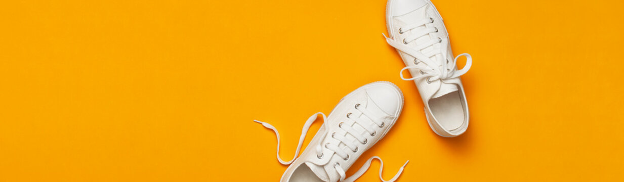 White female fashion sneakers on yellow orange background. Flat lay top view copy space. Women's shoes. Stylish white sneakers. Fashion blog or magazine concept. Minimalistic shoe background, sport