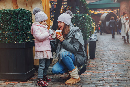 Mother with child girl drinking hot chocolate coffee at Christmas market celebrating New Year holiday. Family outdoor winter activity. Mom and daughter spend time together. Authentic lifestyle.