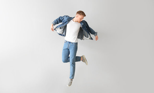 Jumping young man on light background
