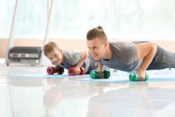 Father and son training together in gym