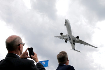 A visitor takes a picture of an Airbus A350-1000 as it performs during the 53rd International Paris Air Show at Le Bourget Airport near Paris