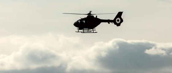 a helicopter flying in an evening cloudscape