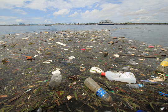 Plastic and styrofoam bottles, bags and food containers dumped in river and flow into sea