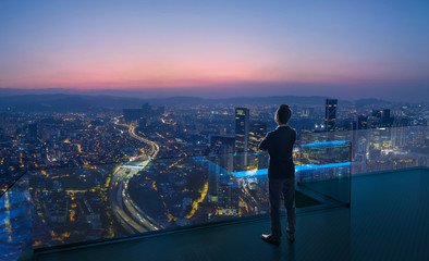Businessman standing on open roof top balcony watching city night view . Business ambition and vision concept . Wall mural