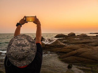 Man taking photos of sunset with mobile phone. Traveler young man is shooting video of beautiful sunset landscape on mobile phone camera. Summer vacation travel and holiday.