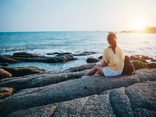 Woman looking to the sea and sitting on the rock. Hipster woman travel at the beach. Fotomurais