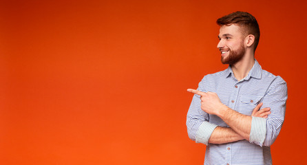 Young redhaired guy showing with finger on copy space Wall mural