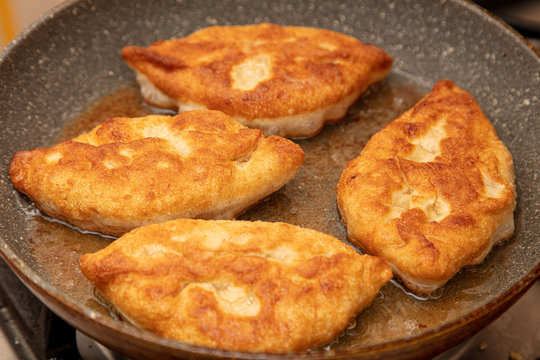 Patties are fried in oil in a pan