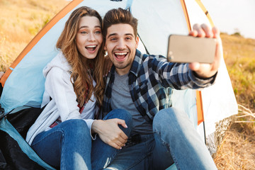 Happy young loving couple outside in free alternative vacation camping take a selfie by phone.