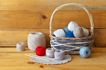 Cotton yarn balls for hand knitting in a wicker basket, handmade napkin and crochet hooks on a wooden background. Handicrafts, needlework and hobbies. Rustic still life, close-up, copy space