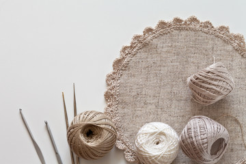 Needlework. Napkin, hand knotted with openwork lace, the crochet hooks and balls of cotton yarn beige color on a white table. Top view, close-up, flat lay, copy space