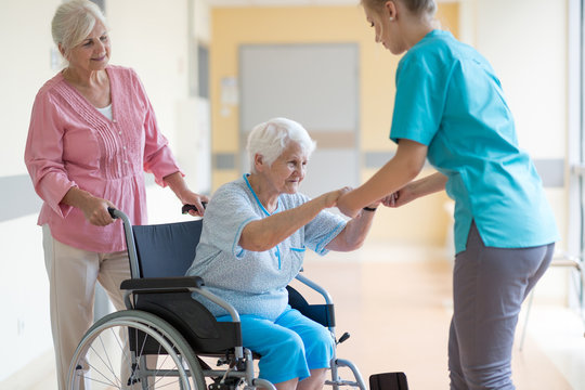 Nurse helping elderly woman in wheelchair