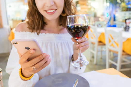Woman drinking red wine at the restaurant and using special app in her smartphone