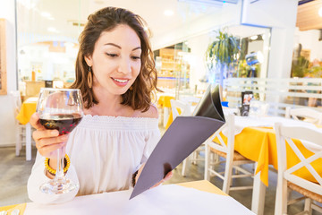Woman drinking wine and reading menu in restaurant