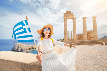 Zelfklevend Fotobehang Athene Woman Traveler with backpack Enjoying great view og the ancient Greek Acropolis with flag in hands