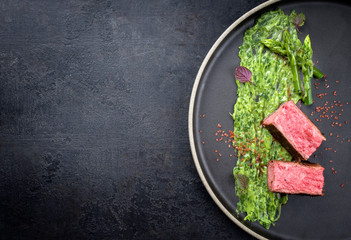 Blanched green asparagus tips with barbecue dry aged wagyu fillet steak and avocado coriander relish as top view on a modern design plate with copy space left