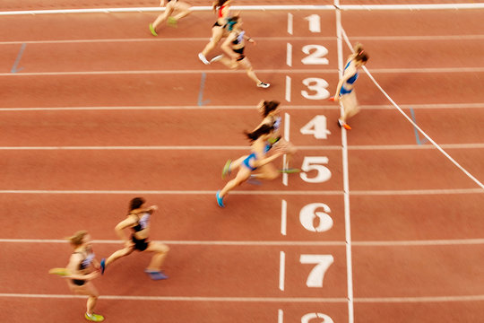 finish line woman runners sprinters run 100 meters motion blur