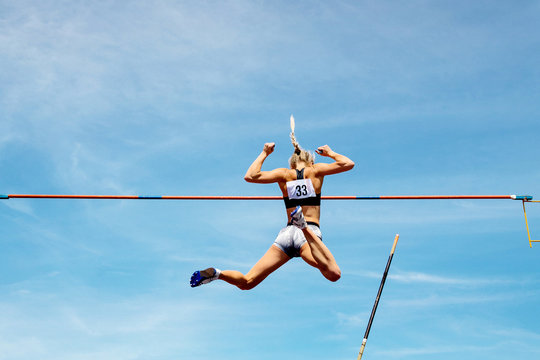 pole vault woman vaulter successful attempt to fly background in blue sky